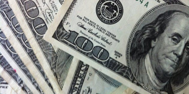 A pile of money - $100 dollar bills. Focus is on the $100 with Benjamin Franklin looking in from the...