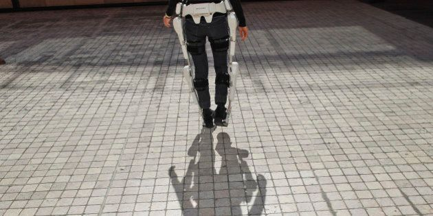 A woman walks with the Robot Suit HAL during the Innorobo European summit, an event dedicated to the robotics industry, in Lyon, central France, Thursday, March 15, 2012. The Robot Suit HAL, created by Cyberdyne in Japan, is a cyborg-type robot which can expand and improve physical capability. HAL is expected to be applied in various fields such as rehabilitation support and physical training support in medical field, support for disabled people, heavy labour support at factories, and rescue support at disaster sites. (AP Photo/Laurent Cipriani)