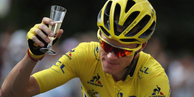 Britain's Chris Froome, wearing the overall leader's yellow jersey, celebrates with a glass of champagne...