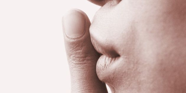 close-up of a persons finger on the lips (sepia)