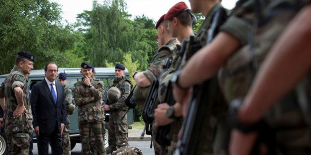 French President Francois Hollande reviews troops at the Army base and command centre for France's 'Vigipirate'...