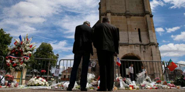 Men stand near flowers left in tribute to French priest Father Jacques Hamel outside the parish church...