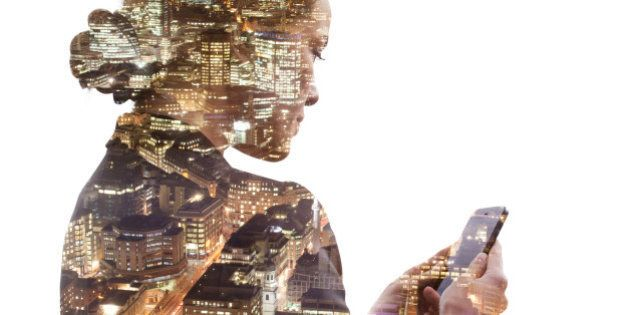 Double exposure of a business woman using a smart phone, and a view of the financial district of the...