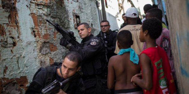 Special Operations Battalion (BOPE) Police officers patrol as residents move about the Sao Carlos slum...