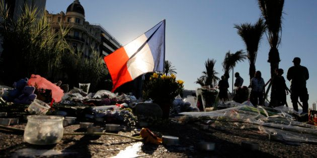FILE - In this Sunday, July 17, 2016 file photo, a French flag stands stall amongst a floral tribute...