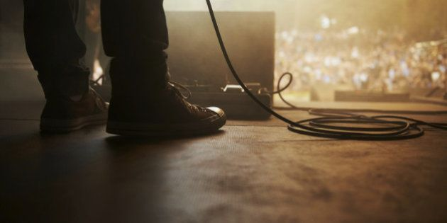 Cropped shot of a musician's feet on stage at an outdoor music festival