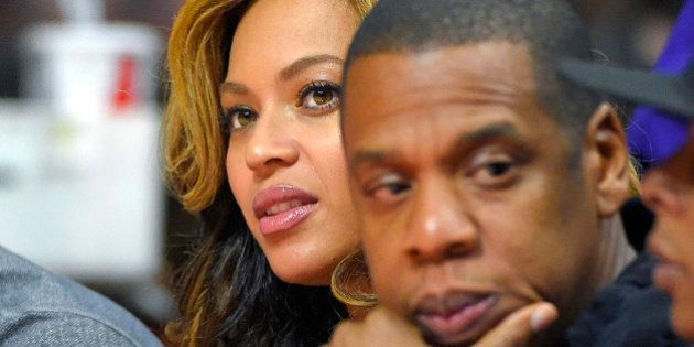 Singer Beyonce, left, and Jay-Z attend the first half of an NBA basketball game between the Los Angeles...
