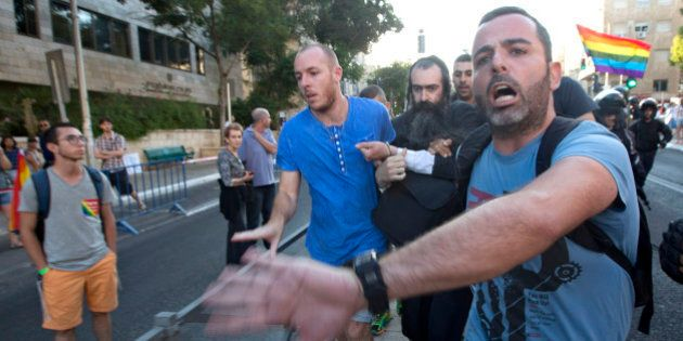 Plainclothes Israeli police detain an ultra-Orthodox Jew after he attacked people with a knife during...