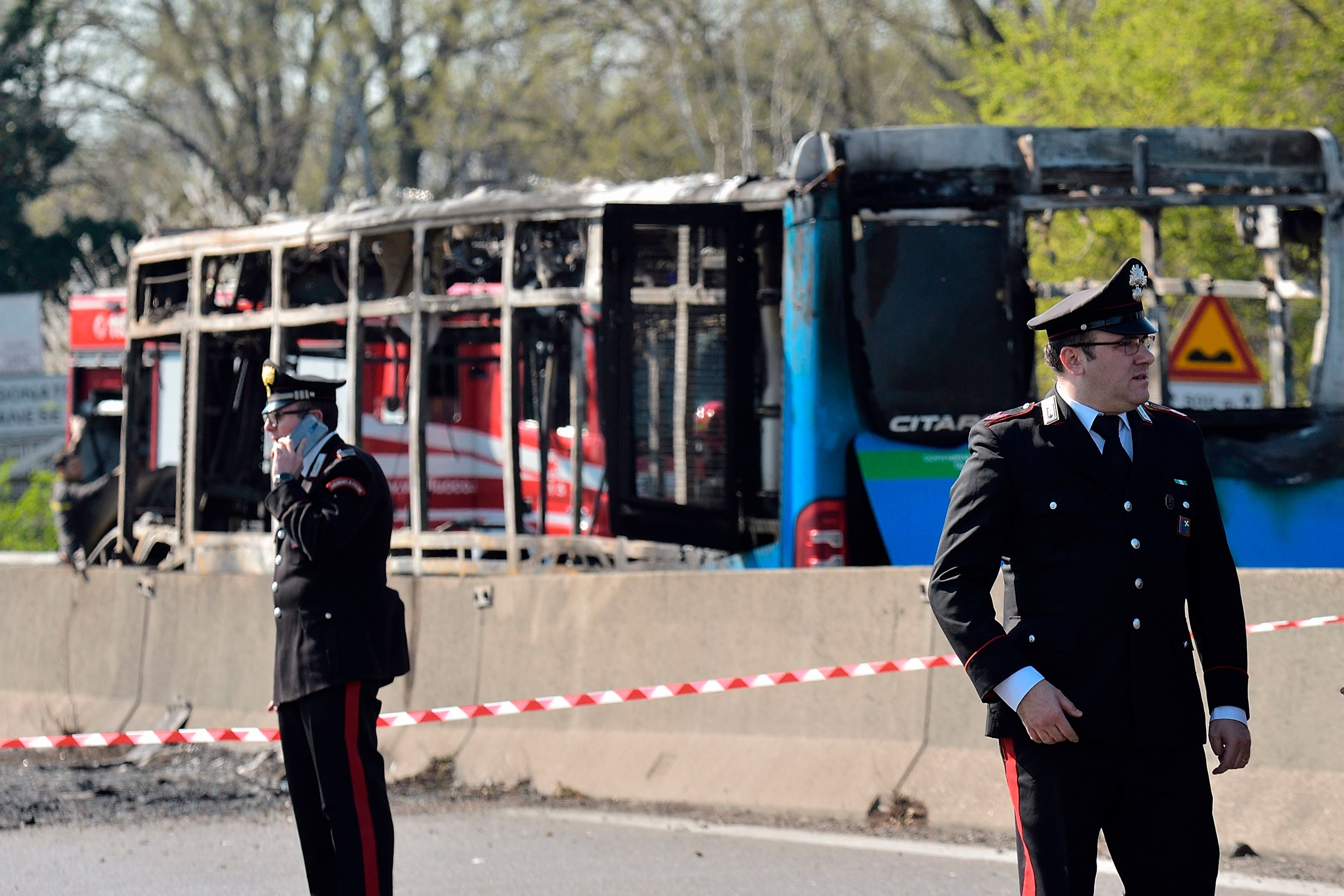 Itaian policemen work by the wreckage of a school bus that was transporting some 50 children on March 20, 2019 after it was torched by the bus' driver, in San Donato Milanese, southeast of Milan. - Italian police rescued some 50 children on March 20, 2019 after their driver threatened to torch their school bus which he doused with petrol, the authorities said. 'It is a miracle, it could have been carnage. The police were outstanding, blocking the bus and getting the children off,' said Milan prosecutor Francesco Greco, who added that he could not rule out a terrorist connection. (Photo by Flavio LO SCALZO / AFP)        (Photo credit should read FLAVIO LO SCALZO/AFP/Getty Images)