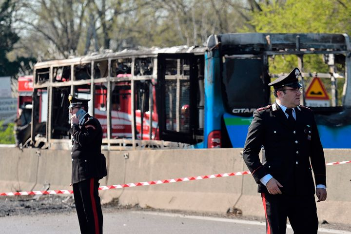 Italian policemen work by the wreckage of a school bus that was transporting some 50 children on March 20, 2019, in San Donat