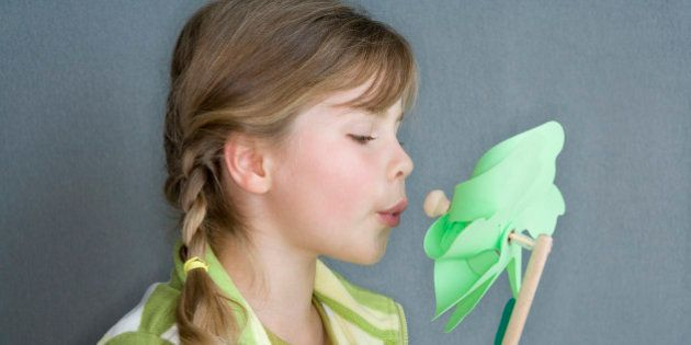 pigtailed girl blowing green windmill