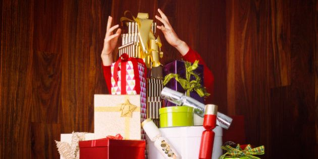 Man reaching for gift on large pile of christmas