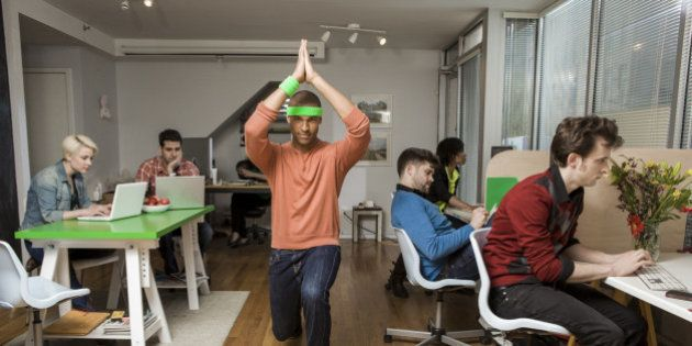 Young man exercising while colleagues work