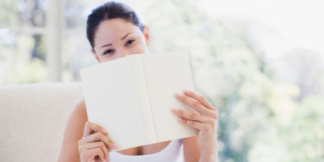 Woman holding book over mouth
