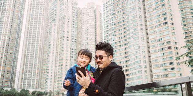 Young handsome dad carrying lovely little daughter while both having fun using a smartphone together...