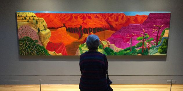 This Feb. 20, 2016 photo shows a visitor gazing at David Hockney's depiction of the Grand Canyon in a show called