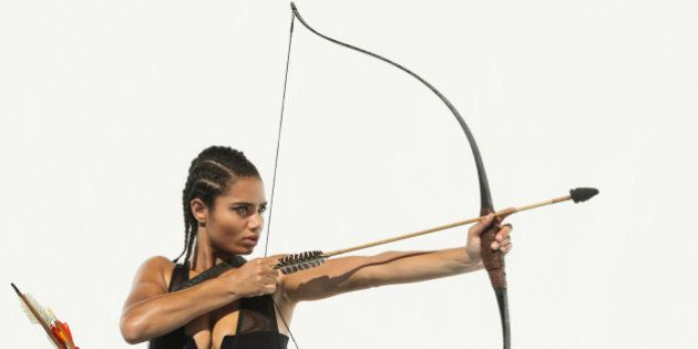 Mixed race woman aiming bow and