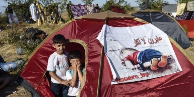 Children sit inside a tent bearing an image of three-year-old Aylan Kurdi, the Syrian toddler who's body...