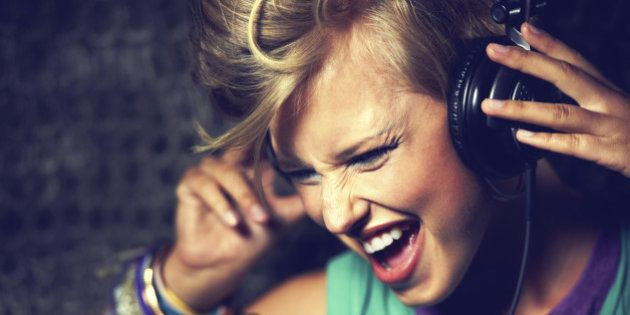 Close-up studio shot of an attractive trendy young woman with her hands on her headset