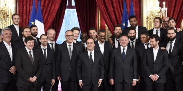 French President Francois Hollande (C) poses with French handball national team players and staff members...