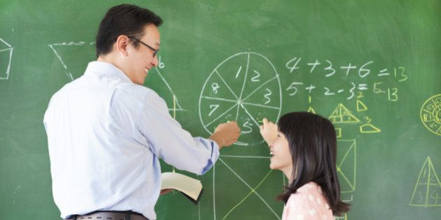 Teacher teach student how to solve the math questions in the classroom