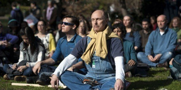 Demonstrators meditate before taking part in The People's Climate march in central London on March 7,...