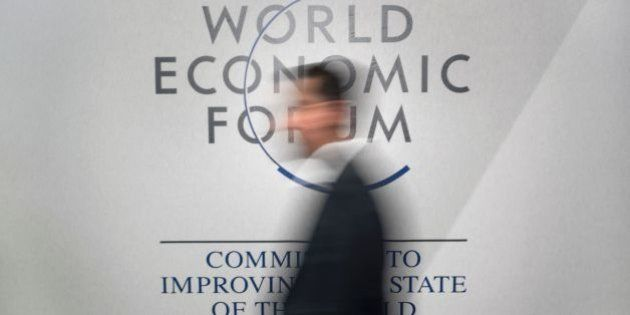 A participant walks past a logo during the World Economic Forum (WEF) annual meeting in Davos, on January...