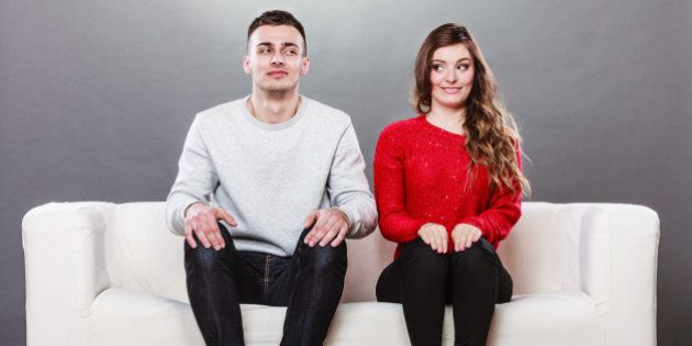 Shy woman and man sitting on sofa couch next each other. First date. Attractive girl and handsome guy...
