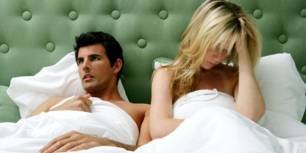 Young couple having argument in bed.