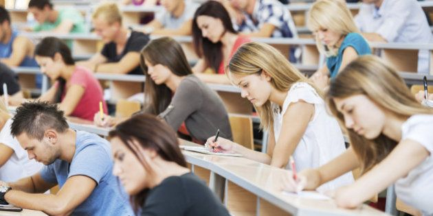 'Group of college students in the university amphitheatre, they are sitting and doing an exam.'