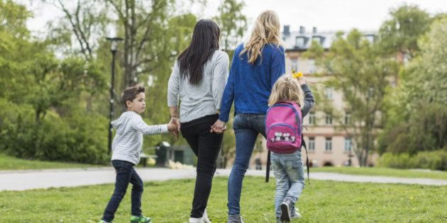 Rear view of female homosexual family walking in