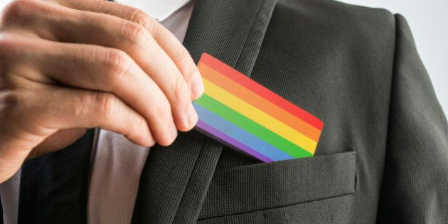 Man withdrawing a wooden card painted as the gay pride flag from his suit pocket, close up of his hand.