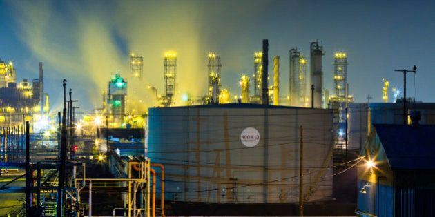 Hundreds of various colored safety lights illuminate rising vapor trails at a large oil refinery complex...