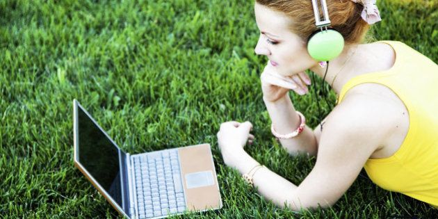 Young woman having rest on grass with laptop