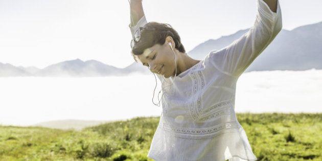Young woman dancing in field, Tyrol, Austria