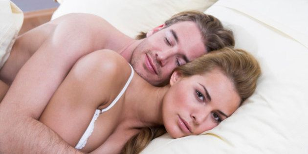 young couple lying in bed together woman looking