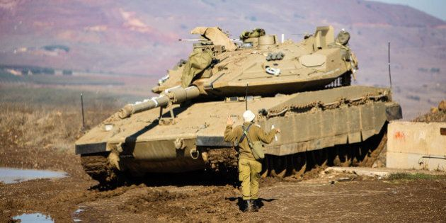 A soldier from the IDF's Artillery Corps prepares a Merkava tank on Israel's border with Syria in the...