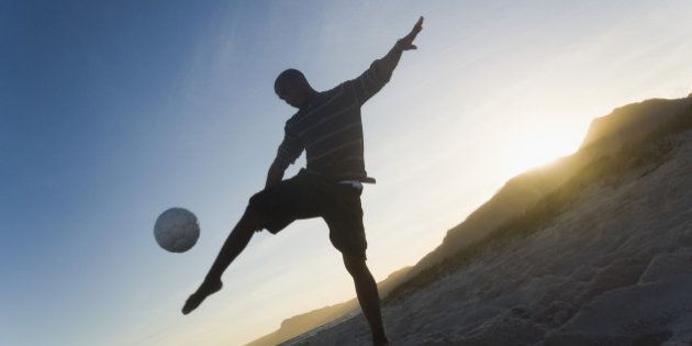 Man playing soccer on the beach, Cape Town, Western Cape Province, South