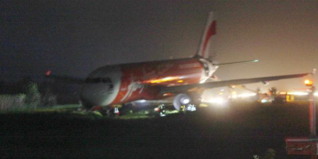 An AirAsia passenger plane sits on the grassy portion of the runway after overshooting upon landing in...