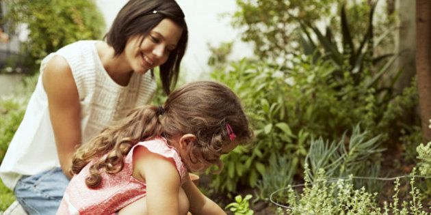 Mother and daughter planting together in garden