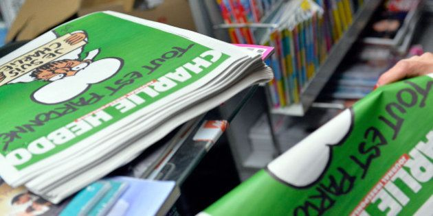 UNSPECIFIED, UNSPECIFIED - JANUARY 14: A woman buys a copy of the new edition of Charlie Hebdo magazine...