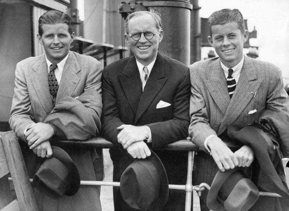 """Joseph Patrick Kennedy (au milieu sur la photo) est considéré comme le patriarche de la famille. Surnommé """"Joe"""", le père de JFK a d'abord prospéré dans les affaires avant de se tourner vers la politique. Proche de Roosevelt, il sera nommé ambassadeur des Etats-Unis au Royaume-Uni entre 1938 et 1940. Marié à Rose Fitzgerald, ils auront ensemble neuf enfants."""