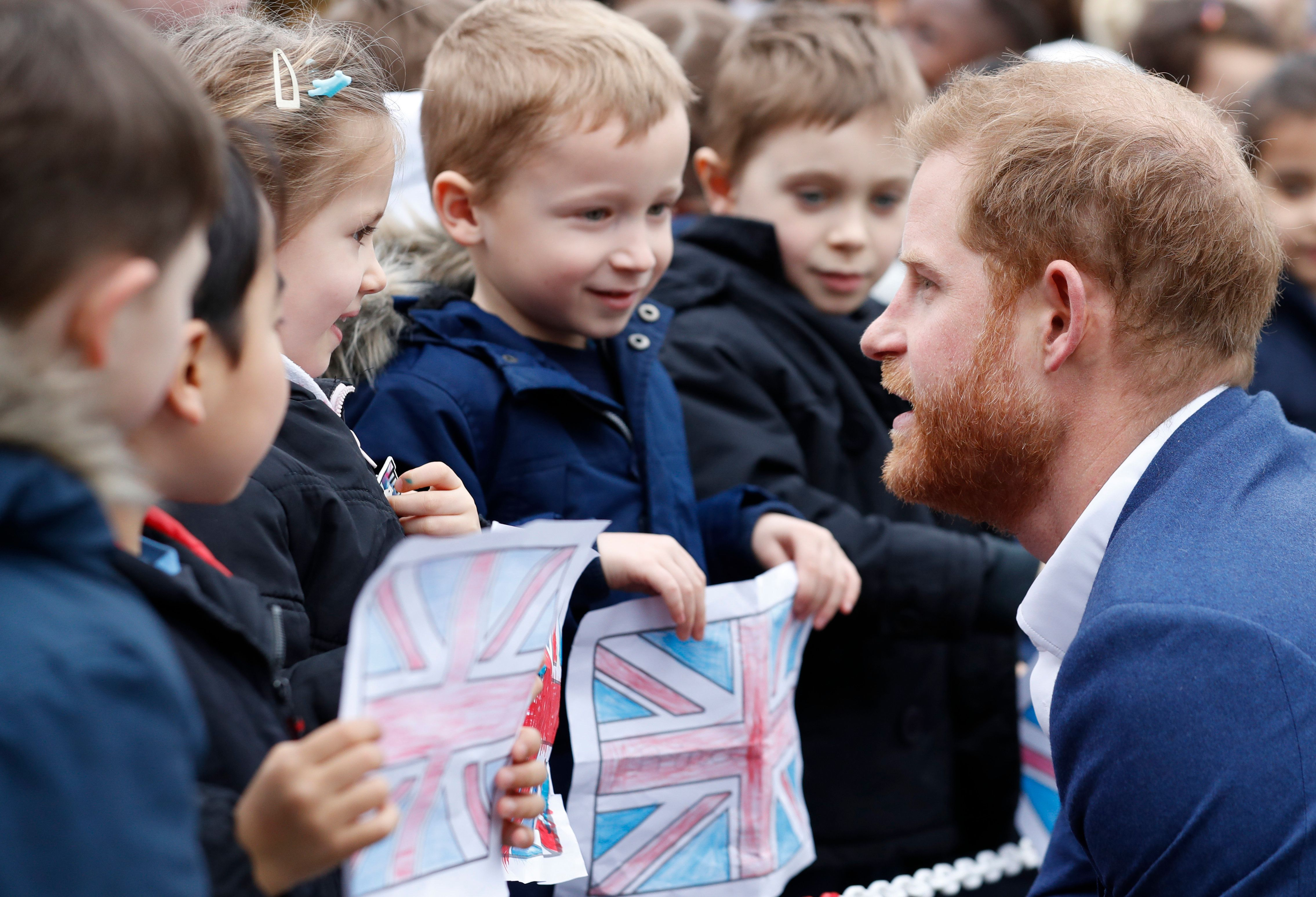 Prince Harry greets pupils from St. Vincent's Catholic Primary School before planting a tree.