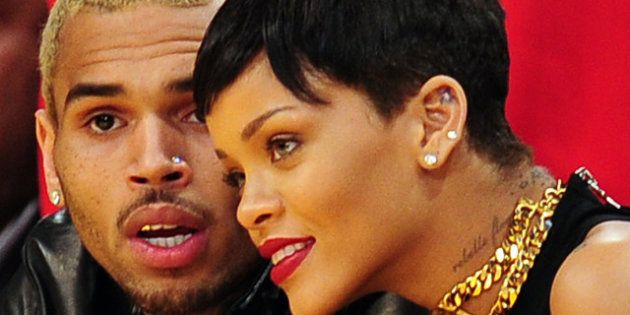 Rihanna (R) and Chris Brown attend a game between the New York Knicks and the Los Angeles Lakers during...