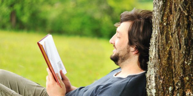 young relaxed man reading book...