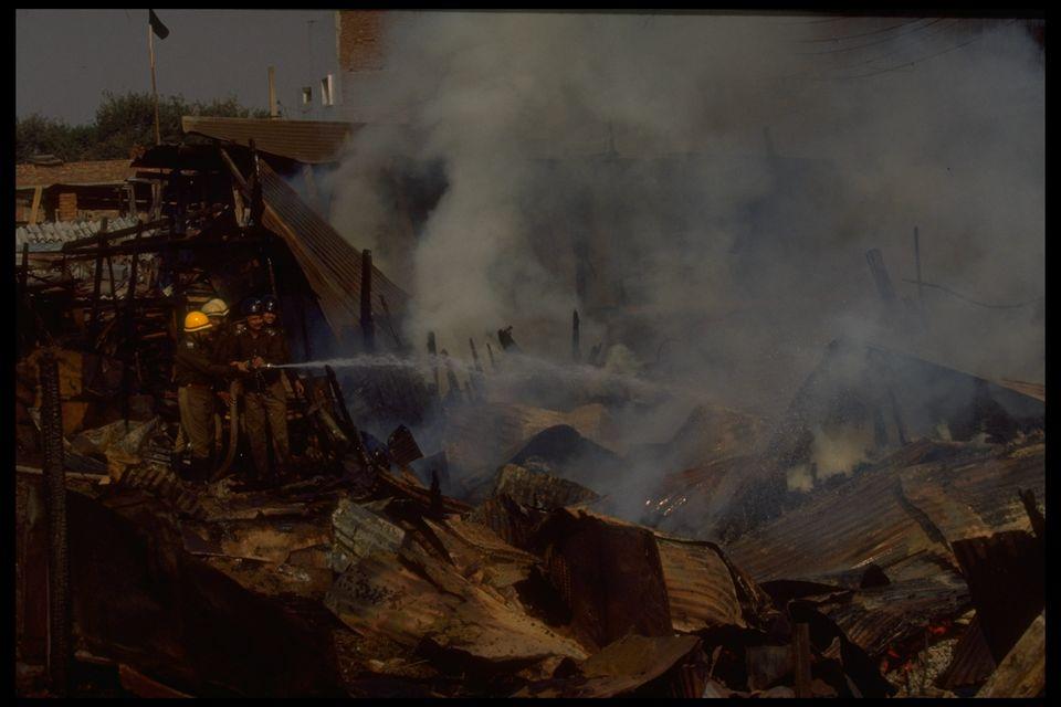 Firemen battling blazes set by Hindu mobs burning Muslim homes in rioting sparked by razing of Babri
