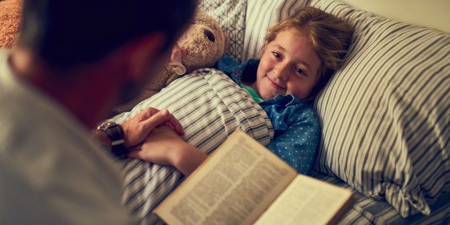 Cropped shot of a father reading a bedtime story to his little daughter at