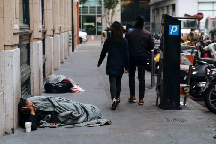 People walk by homeless people sleeping on the streets of San Francisco, California -- Aug. 23, 2018.
