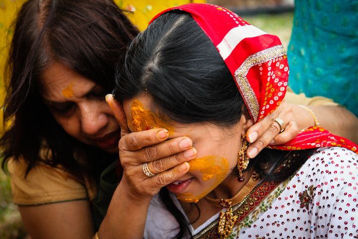 Women during the haldi ceremony, in which people rub turmeric mixtures on the bride and groom to promote bright complexions for their wedding.