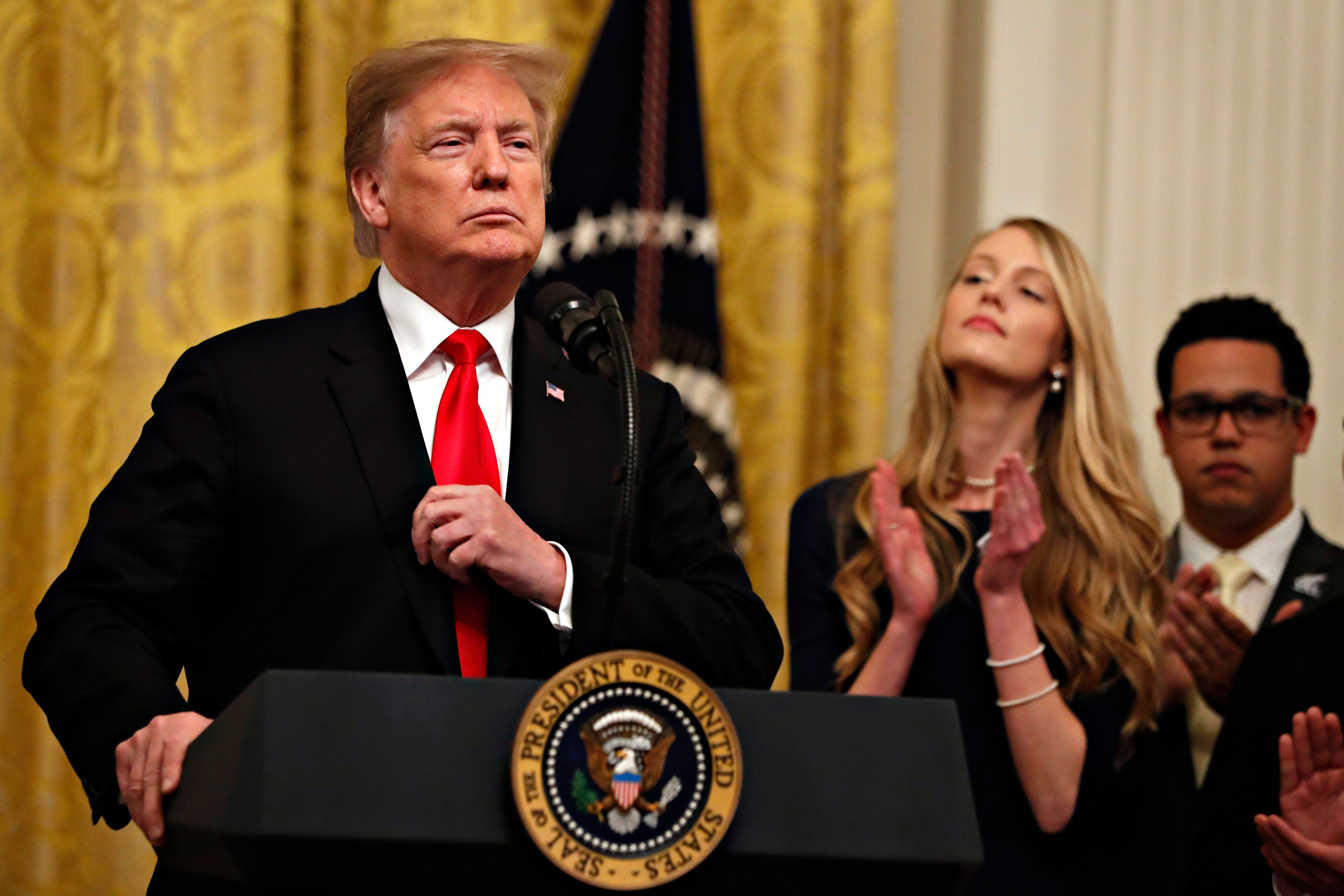 President Donald Trump adjusts his blazer as he speaks before signing an executive order requiring colleges to certify that their policies support free speech as a condition of receiving federal research grants, Thursday March 21, 2019, in the East Room of the White House in Washington. (AP Photo/Jacquelyn Martin)